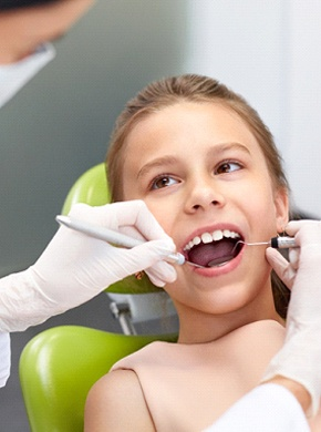 Kids dentist completing a checkup on a young patient.