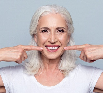 Older woman with dental implant bridge in Manchester pointing to smile.