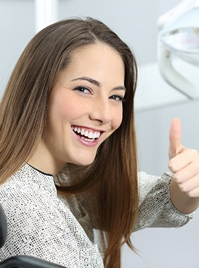 young attractive woman in dentist chair happy giving thumb up