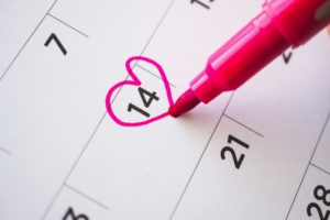 person drawing a heart around the date February 14th on a calendar