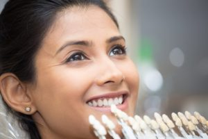 Smiling woman getting porcelain veneers in Manchester
